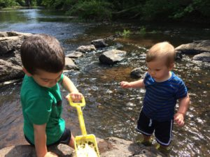 Two boys playing in river; one is holding a yellow shovel and digging in the sand