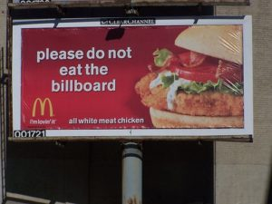 "Billboard featuring advertisement for McDonald's: text reads ""please do not eat the billboard""; to the right of text is a picture of a fried chicken sandwich; the McDonalds logo is in the bottom left-hand corner"